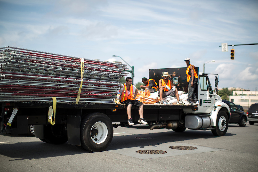 Workers ride on the back of a truck carrying chain-link fencing ahead of the Democratic National Convention on Monday, September 3, 2012 in Charlotte, NC.