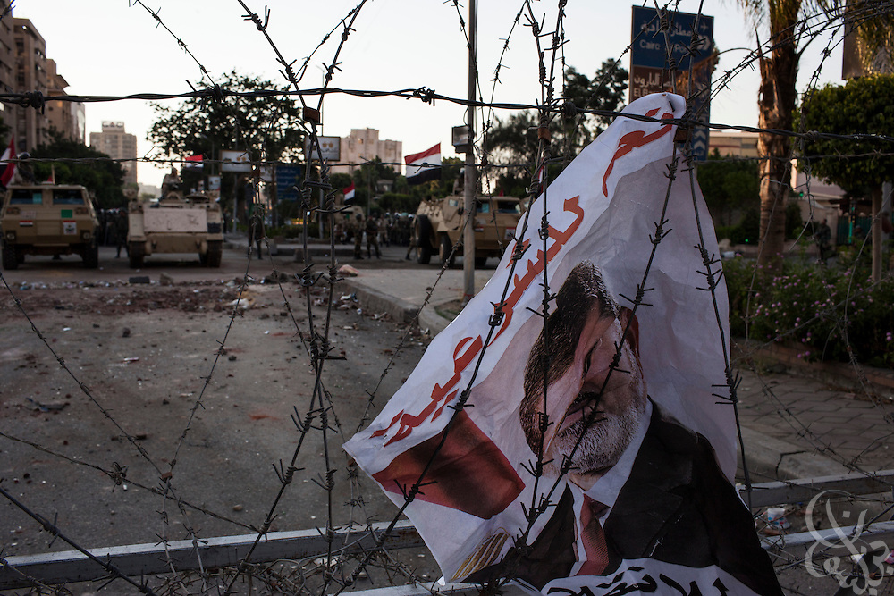 A poster of deposed Egyptian president Mohamed Morsi remains on a barb wired fence near members of the military and police force at the edge of the now month long demonstrations and sit-in around the Rabaah al-Adawia mosque and square in the Nasr City district of Cairo Friday July 26, 2013.  The supporters are demanding the reinstatement of the deposed President and are opposed to the Egyptian military, which they say has undertaken an undemocratic coup.