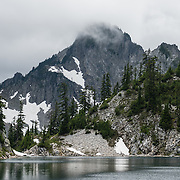 Kaleetan Peak (6259 ft / 1908 m) rises into cloud above Gem Lake in Alpine Lakes Wilderness Area in the Cascade Range of Washington, USA. In mid July, we hiked to Gem Lake 10 miles round trip with 2800 feet cumulative gain along Snow Lake Trail #1013 in Mt. Baker-Snoqualmie National Forest. Take Interstate 90 Exit #52 westbound or Exit #53 eastbound and follow signs to Alpental Road ski area parking lot and trailhead. To avoid crowds at this popular trail, start early and avoid sunny weekends. The trail down from the saddle viewpoint to Snow Lake is often snow covered through July 4.
