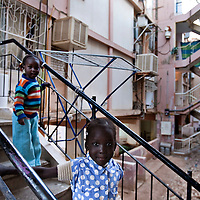 """Sudanese refugee girls plays in the cage staircase of the sinsin building  on February 28 2011 in Eilat. The municipality hung 1,500 red flags around the city as a sign of warning and put up hundreds of banners reading: """"Protecting our home, the residents of Eilat are drawing the line on infiltration."""" Eilat Mayor Meir Yitzhak Halevi said that 10 percent of the city's population was currently made up of migrants and that the residents feel that the city has been conquered...Photo by Olivier Fitoussi."""