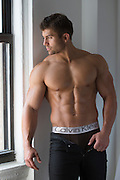 hot bodybuilder taking off his pants while standing by a window
