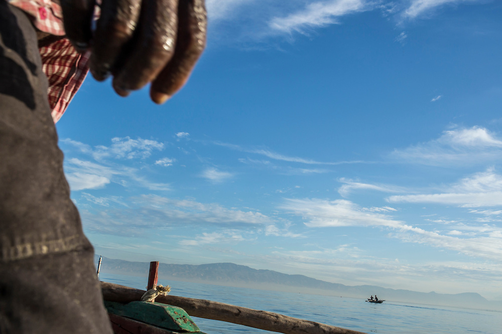 Fisherman Jean Claude Pierre, looks out from his boat at another fishing crew in between checking nets on Monday, December 15, 2014 in Port-au-Prince, Haiti.