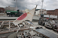 A Japanese flag flies over the remains of the town of Onagawa, which was obliterated by the March 11th tsunami, in Onagawa, Tohoku region, Japan, on Friday 17th June 2011. There are now fears for the pollution and health risks that the debris of such towns now holds, including the releasing into the air of asbestos dust.