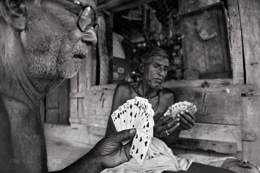 Elderly people spend their time with playing cards. Image © Mohammad Rakibul Hasan/Falcon Photo Agency