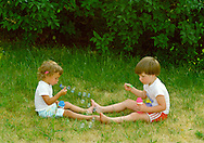 Brother and Sister playing together, blowing bubbles