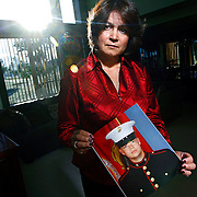 "SHOT 6/11/08 6:51:47 PM - Veronica DeLuccie, 48, of Brighton, Co. poses with a portrait of her 20 year-old son Matthew Shane Armendariz at their home in Brighton on Wednesday June 11, 2008. Armendariz is  a Marine stationed in Fallujah, Iraq and has a wife and 18 month-old son back in Colorado. DeLuccie said she had hoped he wouldn't enlist but supports him nonetheless and said, ""every day I pretend I don't know where he's at"". She added that it was his life long dream to serve in the military and he sees it as a way to provide for his family..(Photo by Marc Piscotty / WpN)"