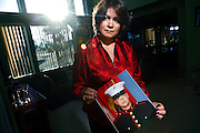"""SHOT 6/11/08 6:51:47 PM - Veronica DeLuccie, 48, of Brighton, Co. poses with a portrait of her 20 year-old son Matthew Shane Armendariz at their home in Brighton on Wednesday June 11, 2008. Armendariz is  a Marine stationed in Fallujah, Iraq and has a wife and 18 month-old son back in Colorado. DeLuccie said she had hoped he wouldn't enlist but supports him nonetheless and said, """"every day I pretend I don't know where he's at"""". She added that it was his life long dream to serve in the military and he sees it as a way to provide for his family..(Photo by Marc Piscotty / WpN)"""