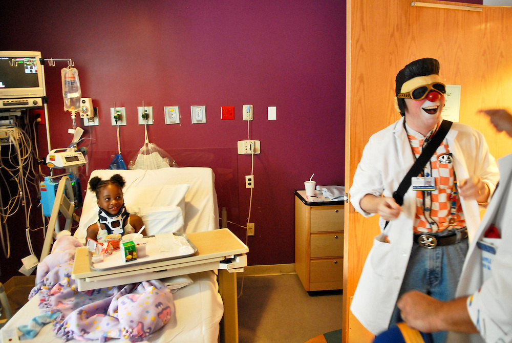 """(staff photo by Matt Roth)..""""I must have one of the only jobs in the world where I can claim an Elvis Mask on my taxes."""" Greg May, a Columbia-based variety entertainer, uses his newly bought prop to bring a smile to the face of six-year-old Taylor Young, from Ellicott City, one of the sick children he and his partner Bill Boots, from Arbutus, entertain at Johns Hopkins Hospital Wednesday July 19, 2006, as part of a program put on through the Big Apple Circus Clown Care program."""