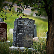 """SHOT 8/7/09 7:35:20 PM -  The Golden Hill Cemetery, one of the few sites along Colfax on the National Register of Historic Places, is the final home to more than 2,000 people who died of tuberculosis in the early 1900s. The Jewish cemetery, 12000 W. Colfax, has more than 8,000 gravestones. Colfax Avenue is the main street that runs east and west through the Denver-Aurora metropolitan area in Colorado. As U.S. Highway 40, it was one of two principal highways serving Denver before the Interstate Highway System was constructed. In the local street system, it lies 15 blocks north of the zero point (Ellsworth Avenue, one block south of 1st Avenue). For that reason it would normally be known as """"15th Avenue"""" but the street was named for the 19th-century politician Schuyler Colfax. On the east it passes through the city of Aurora, then Denver, and on the west, through Lakewood and the southern part of Golden. Colloquially, the arterial is referred to simply as """"Colfax"""", a name that has become associated with prostitution, crime, and a dense concentration of liquor stores and inexpensive bars. Playboy magazine once called Colfax """"the longest, wickedest street in America."""" However, such activities are actually isolated to short stretches of the 26-mile (42 km) length of the street. Periodically, Colfax undergoes redevelopment by the municipalities along its course that bring in new housing, trendy businesses and restaurants. Some say that these new developments detract from the character of Colfax, while others worry that they cause gentrification and bring increased traffic to the area. (Photo by Marc Piscotty / © 2009)"""