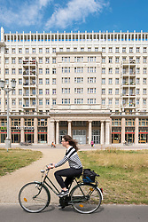 Cyclist rides past historic socialist former East German apartment buildings on Karl Marx Allee in Berlin Germany