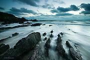Incoming tide over reef at dusk at Aberffraw beach, Isle of Anglesey