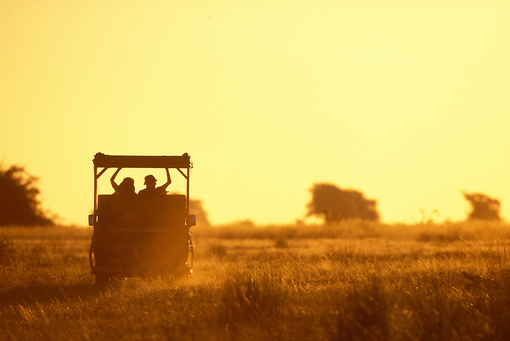 Africa, Botswana, Chobe National Park, Tourists on sunset game viewing drive during safari near Chobe River