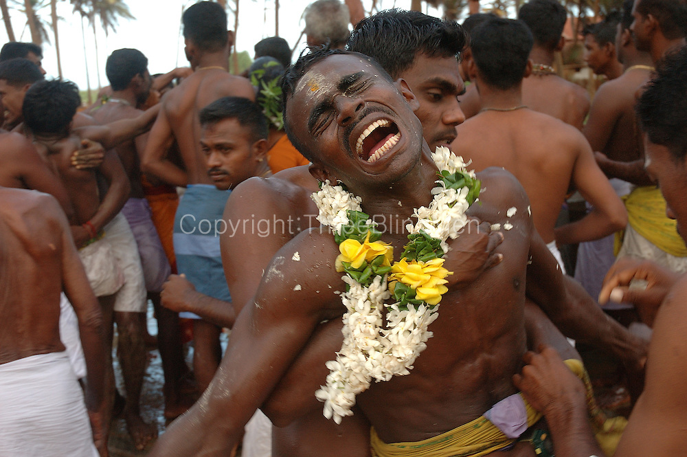 Sri Lanka. Udappuwa festival. The village, men and women, gather at the Mariamman Kovil in the north of the village. Here they bathe at the well, fall into a deep trance, dance kavadi, & then move south to the main Vishnu Kovil, stopping at a small beach Kataragama shrine on the way...The trance is very strong, they often have to be restrained by family & friends, screaming as this is done.