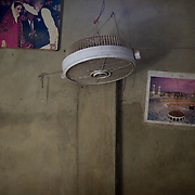 A ventilator hangs between a poster of Benezir Bhutto and the Kaaba (cube) of Mecca  on the wall of the delivery room where Sherbano conducts her home deliveries. <br /> Due to lack of electricity and heavy power cuts, the ventilator hardly ever brings any relief to the woman in labour. Rehri Goth, Karachi, Pakistan, 2011