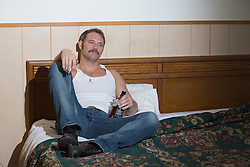 lonely man in a cheap motel room sitting in bed with a cigarette in one hand and a bottle of alcohol in the other