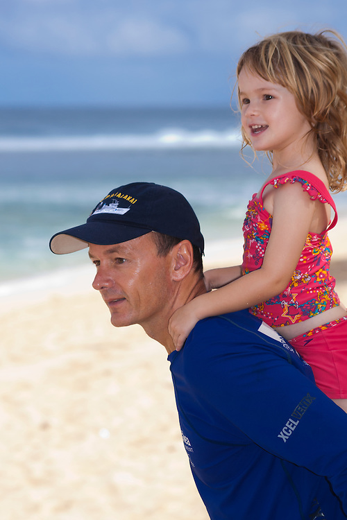 A father with his small daughter on his back on the beach looking out at the surf in Hawaii