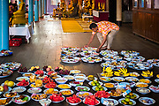 "A local man loads food trays that will presented to the monks for blessing, which is a way of giving alms. The monks will eat first then the congregation will share a ""potluck"" breakfast. Nakhon Nayok, Thailand, April 13, 2017. PHOTO BY LEE CRAKER"