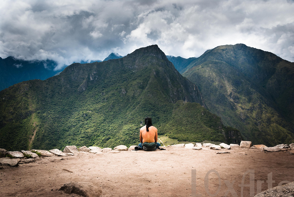 Man meditates on a terace on Wayna Picchu, overlooking the Machu Picchu citadel, on a dramatically cloudy day. The image is available for commercial licensing through Arcangel Images. ID# AA1644983 . Contact LOxArte for Fine Art Prints.