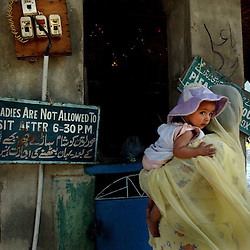 KASHMIR,INDIA: A Kashmiri Muslim woman and her child visit a Shiite shrine in Srinagar, the Indian held summer capital of the state of Jammu and Kashmir .  A sign reads that ladies are not allowed to enter the shrine after 6:30 pm.  Islamic guerrillas have been fighting for independence of the Indian-controlled portion of Kashmir since 1989 but for the first time in 13 years, Kashmiris living in Srinagar have enjoyed a fragile peace and boon in tourism.