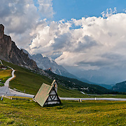 Crepuscular rays shine on Gasthaus Passo di Giau (2236 meters), where you can explore scenic trails of the Dolomites (Dolomiti, a part of the Southern Limestone Alps), northern Italy, Europe. The Dolomites were declared a natural World Heritage Site (2009) by UNESCO. Panorama stitched from 12 overlapping photos. Published in Wilderness Travel 2015 Catalog of Adventures.