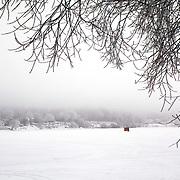 Ice fishing shack  through the frozen fog on Lake Mendota in Madison, Wisconsin.