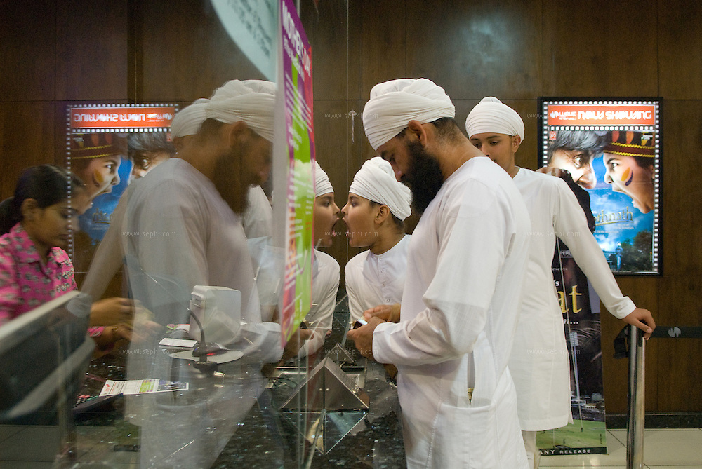 A Sikh father and his two sons at the box office for the Wave Cinema complex at Ludhiana's West End Mall, Punjab, India