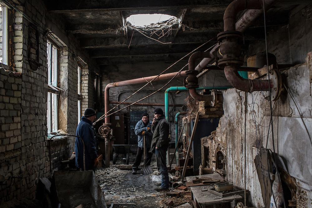 Vladimir Vertsanov, Petro Goncharenko, and Vladimir Iermilov, from left, take a break from shoveling coal for heating at the village school on Thursday, February 11, 2016 in Troitske, Ukraine.