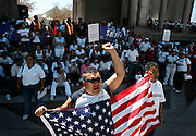 Sandro Lopez (left) and Juan Carlo Garcia (right), both of Denver, lead a cheer while displaying an American flag during a National Day of Action rally at Civic Center Park in Downtown Denver, Co. Monday April 10, 2006. The event coincided with other rallies across the nation to protest proposed immigration reform that Congress is currently considering. About 2,000 people turned out at the rally to make their voices heard on the issue. Lopez, 39, is originally from El Salvador and Garcia, 26, was born in Honduras..(MARC PISCOTTY/ © 2006)