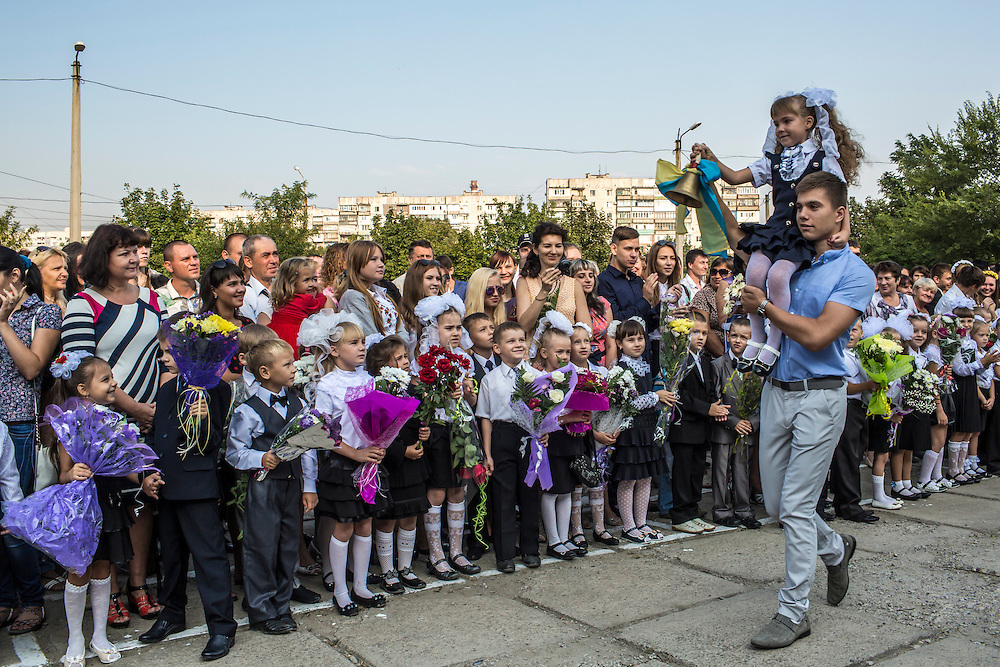 MARIUPOL, UKRAINE - SEPTEMBER 1, 2015: A girl rings a bell to signify the start of the new school year during a ceremony at School 68 in Mariupol, Ukraine. On January 24 of this year, shelling in the same neighborhood killed 31 people, all civilians, and while much recent fighting has been concentrated near Mariupol, a drop in ceasefire violations in the past few days has been credited to a desire to not interfere with the start of the new school year. CREDIT: Brendan Hoffman for The New York Times