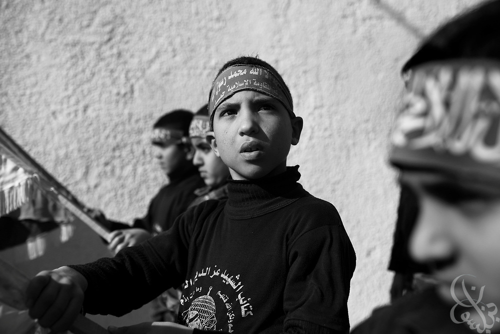 """Palestinian boys carry HAMAS banners during a """"Victory"""" parade thrown by militant Palestinian political group HAMAS January 20, 2009 in Gaza City. Several thousand marchers celebrated what HAMAS called the defeat of Israel during the recent 21 day offensive by Israeli forces against HAMAS fighters. During the operation more than 1500 Palestinians were killed and more than 4000 homes destroyed in the narrow Gaza Strip..."""