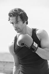 good looking man with boxing gloves outdoors