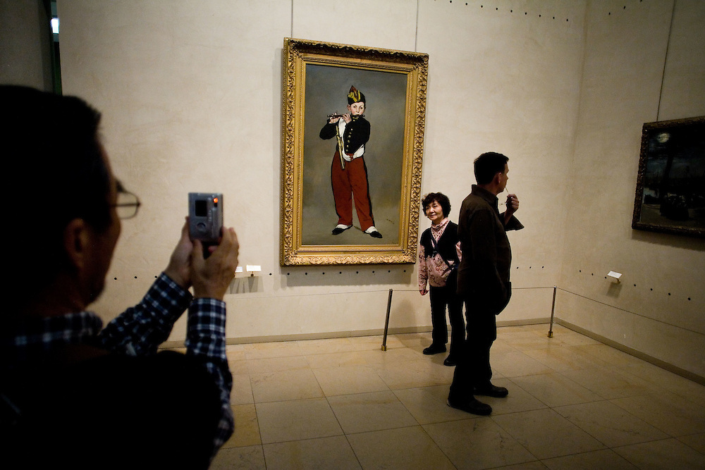 A woman stands by Edouard Manet's painting 'Young Flautist, or The Fifer' at The Musée d'Orsay in Paris, Tuesday, Sept. 16, 2008. (ivan gonzalez)
