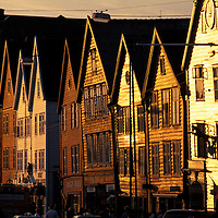 Europe, Norway. Sunset reflects off buildings in Bergen's Bryggen district along the city's waterfront