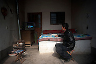 Cotton farmer Yu Ji watches television in his home in the town of Huji in the province of Shandong, China, Friday, Jan. 28, 2011. Despite record cotton prices last year, some farmers liek Mr. Yu are storing their harvest of cotton and are holding out for even higher prices, hoping to help overcome higher costs of fertilizer and labor, which have both risen 20% in the past year..CREDIT:Keith Bedford for The Wall Street Journal.Slug: COTTON..NOTE: A NUMBER OF THE SUBJECTS FAMILY NAME IS YU BECAUSE THE IT IS TAKEN FROM THE VILLAGE NAME OF  THE VILLAGE WHICH I S YUQIAO NOT BECAUSE THEY ARE RELATED.