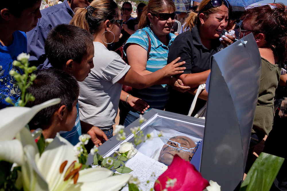 Family take a last look at the body of their dead relative at his funeral in Ciudad Juarez, Chihuahua on May 21, 2010.