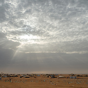 The sun climbs into the sky above the Mbera camp for Malian refugees in southeastern Mauritania on 2 March 2013. The weather is unforgiving, with temperatures climbing into the 40's and and even 50's (Celsius) in the hottest time of the year.