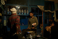 A restaurant owner reaches into his back pocket to make change for a customer in a small Indian Dhabba, Kargil, India