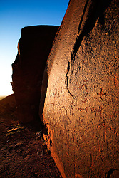 An Ancestral Puebloan (Anasazi) petroglyph panel is bathed in the warm light of the setting sun. Comb Ridge, southern Utah near Bluff.