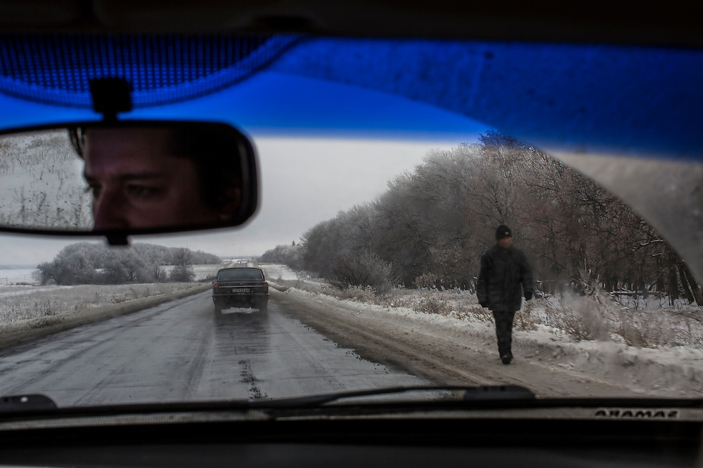 IVANIVKA, UKRAINE - DECEMBER 8, 2014: A man walks along the road between Donetsk and Luhansk in Ivanivka, Ukraine. CREDIT: Brendan Hoffman for The New York Times