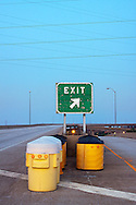 An exit sign directing non-existent motorists towards an off-ramp on the abandoned Cline Avenue structure.