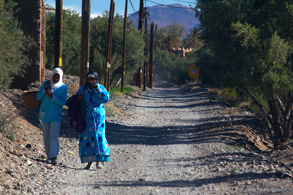 Africa, Morocco, Skoura. Moroccan women in blue walking on road.