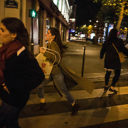 Des personnes qui assistaient à un concert au Bataclan s'échappent dans les rues de Paris, le 13 novembre 2015, à proximité de la salle de concert dans laquelle se déroule au même moment une attaque terroriste.