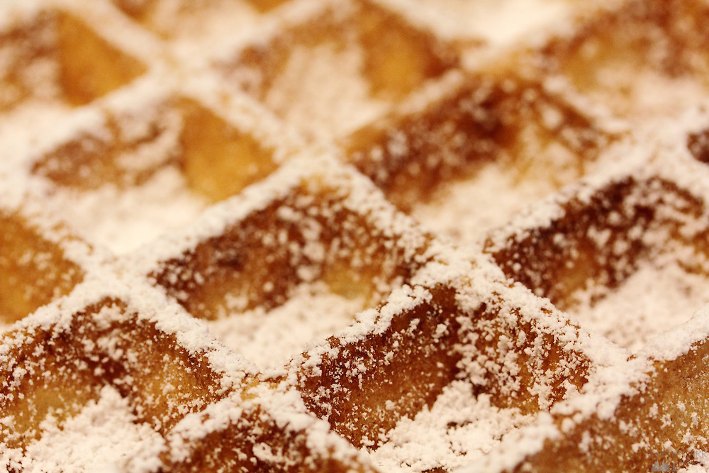 Icing sugar coats a waffle in the Max Café in the old town of Ghent; they only serve waffles between 2 and 6pm and it is packed with locals tucking into this Belgian treat