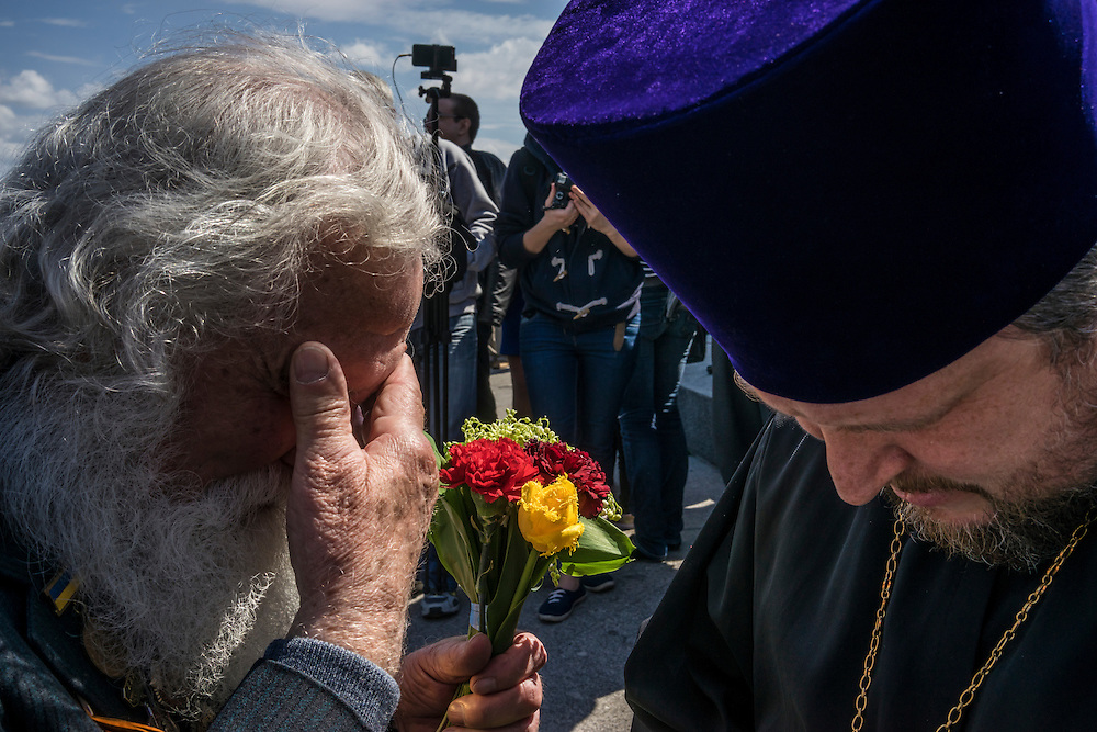 A veteran and an Orthodox priest share a moment during Victory Day commemorations on Saturday, May 9, 2015 in Kyiv, Ukraine.