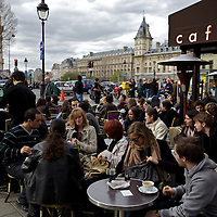 People sit outside a cafe in Paris France