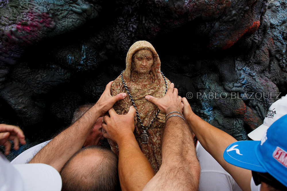 15/08/2016. Fishermen place the image of the Virgin of Palm on a pedestal for worshippers during the yearly Virgin of Palm maritime pilgrimage at El Rinconcillo beach during the yearly Virgin of Palm maritime pilgrimage on August 15, 2016 in Algeciras, Spain. The Our Lady of Palm maritime pilgrimage in Algeciras dates back to 1975 and takes place annually when fishermen rescue the submerged virgin from the deep sea. Worshippers amid thousands of visitors await its arrival at the Rinconcillo beach. The devotion for the Virgin of Palm comes from the seventeenth century when a ship coming from Italy docked at Algeciras port to wait out bad weather. According to legend, once the crew of the ship removed a box with an image of the Virgin from its cargo the weather turned and the sea's tides were calmed. (© Pablo Blazquez)