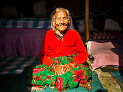 """02 MARCH 2017 - SANKHU, NEPAL: A woman who said she was 100 years old sits in the doorway of her """"temporary"""" shelter in Sankhu. Her home was destroyed in the 2015 earthquake. There is more construction and rebuilding going on in Sankhu, west of central Kathmandu, than in many other parts of the Kathmandu Valley nearly two years after the earthquake of 25 April 2015 that devastated Nepal. In some villages in the Kathmandu valley workers are working by hand to remove ruble and dig out destroyed buildings. About 9,000 people were killed and another 22,000 injured by the earthquake. The epicenter of the earthquake was east of the Gorka district.   PHOTO BY JACK KURTZ"""