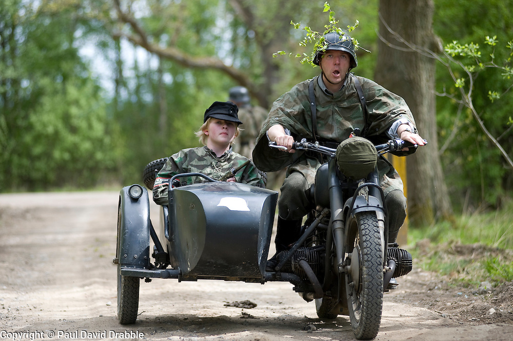 Reenactors from Northern World War Two Association, portraying members of the Grossdeutschland division riding  a motorcycle and sidecar combination during a 24hr private exercise, held at Sutton Grange, near Ripon in Yorkshire. The white steel helmet or Stahlhelm marked on the front of the sidecar is the Gro&szlig;deutschland Division tactical symbol, <br /> 15 May 2010 <br /> Images &copy; Paul David Drabble.