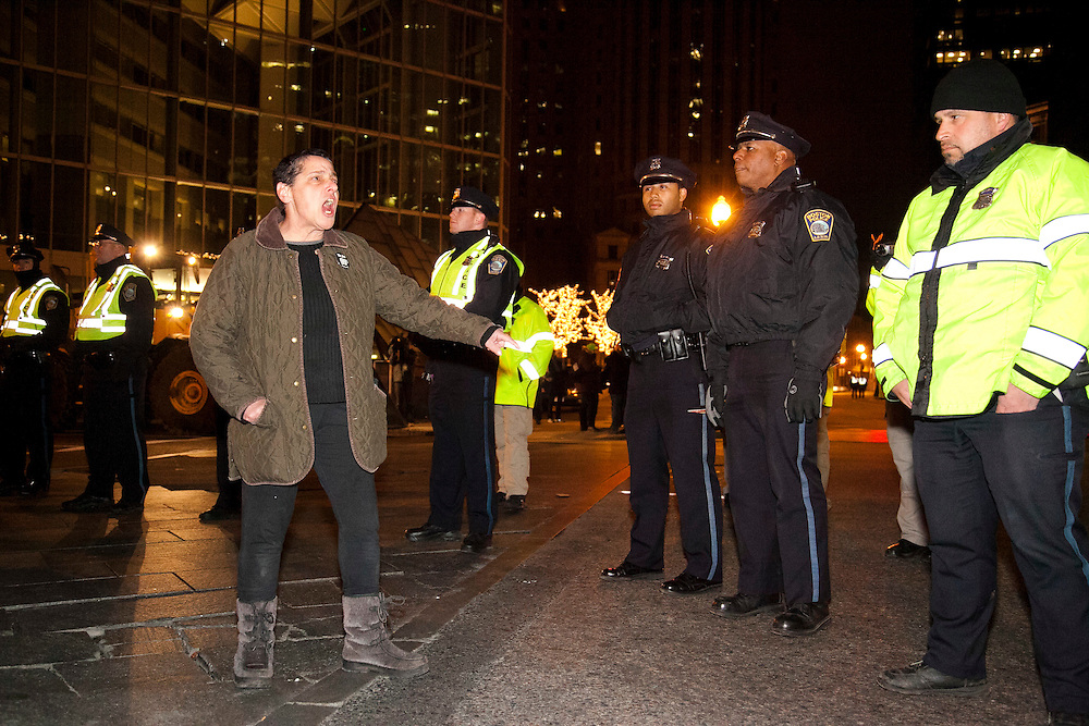 An Occupy Boston member protest against  police officers as the Boston Police tear down the tents and arrest protesters early morning in Boston, Massachusetts, December 10, 2011.
