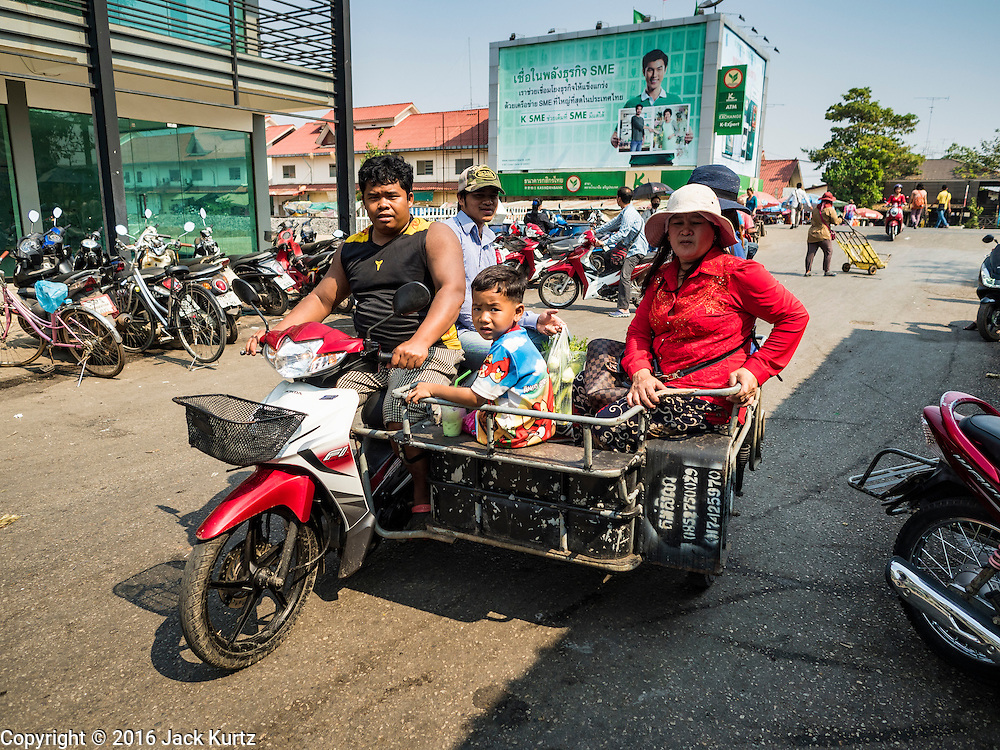 "15 FEBRUARY 2016 - ARANYAPRATHET, SA KAEO, THAILAND: A Cambodian family takes a motorcycle taxi to the crossing point into Cambodia from Aranyaprathet, Thailand. Thais selling bottled water in the border town of Aranyaprathet, opposite Poipet, Cambodia, have reported a surge in sales recently. Cambodian officials told their Thai counterparts that because of the 2016 drought, which is affecting Thailand and Cambodia, there have been spot shortages of drinking water near the Thai-Cambodian and that ""water shortages in Cambodia had prompted people to hoard drinking water from Thailand.""     PHOTO BY JACK KURTZ"